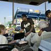 Saints player Jaisen Randolph (center) checks out the barbequed pork tenderloin as he and teammate Corey Freeman (far right) join tailgaters Nancy Peterson (left) and her husband, Peter Boehm (with Freeman), both of St. Paul, for a quick pre-game meal in the parking lot of Midway Stadium on May 16, 2003.  (Pioneer Press: Richard Marshall)