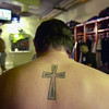"""""""I've always had some sort of cross on me, ever since I was a kid,"""" said St. Paul Saints closer Chris Chavez, getting ready for a game in the cramped Midway Stadium locker room on May 16, 2003. """"Getting the tattoo was no big deal.  Now, keeping my ex-girlfriend's cross on my chain, that was a big deal,"""" he said.  (Pioneer Press: Richard Marshall)<br /> <br /> The St. Paul Saints minor league baseball team has been a part of the Minnesota baseball landscape on and off for close to 100 years. Currently part of the independent Northern League, the Saints provide a place for up-and-coming ballplayers to gain invaluable experience, and for players in their declining years to get in a little ball before calling it quits. For baseball fans, the Saints provide solid competitive play and wonderful on-field entertainment (the team's motto: """"Fun Is Good""""). Most importantly, cozy Midway Stadium in St. Paul, home to the Saints, provides a welcome alternative to the indoor, sterile atmosphere of the Hubert H. Humphrey Metrodome in Minneapolis, home to the Minnesota Twins."""