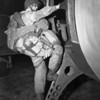 Fully Equipped paratrooper armed with a Thompson submachine gun M1, climbing into a transport plane to go to France as the invasion of Normandy gets under way. At approximately 0200, 6 June 1944, men of two U. S. airborne divisions, as well as elements of a British airborne division, were dropped in vital areas to the rear of German coastal defenses guarding the Normandy beaches from Cherbourg to Caen. By dawn 1,136 heavy bombers of the RAF Bomber Command had dropped 5,853 tons of bombs on selected coastal batteries lining the Bay of the Seine between Cherbourg and Le Havre. Image and caption credit: Center of Military History. U.S. Army.