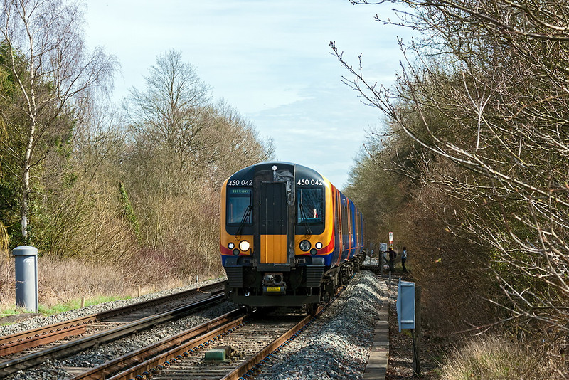 14th Apr 13:  Some walkers stand clear on the foot crossing on the approach to Bentley as 450042, on the 10.49 from Woking, nears the station.