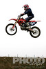 Single motocross rider flying through air, side view