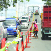TIME TO FIX IT. Workers put up barriers on one lane of the old Mactan-Mandaue bridge. (Sun.Star Photo/Allan Cuizon)