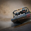 Wanaka Jetsprint Del Tubb<br /> A beautifully crisp image and I like that the viewer can see some of the driver's face rather than just all helmet. I don't feel that the pronounced angle the shot was taken on adds to the action, rather it gives it a slight arty feel which I find somewhat out of place in this type of action shot. Apart from the angle, which is subjective, the shot is very well executed.<br /> Accepted  A grade
