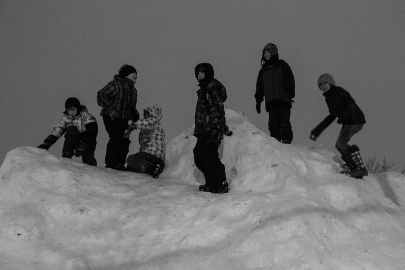 Children playing on snow mound in parking lot at Northern Store in Moosone.