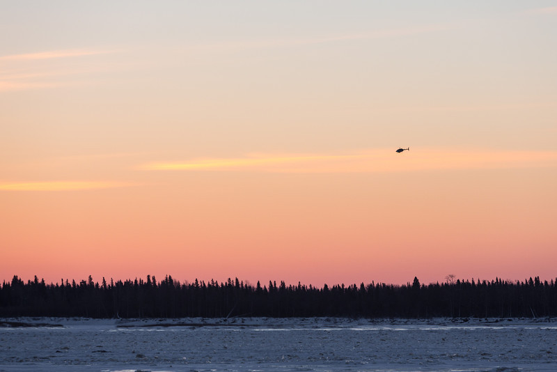 Helicopter heading from Moose Factory to Moosonee.
