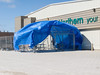 Garden centre being erected at Northern Store in Moosonee, Ontario. High winds lift the tarp.