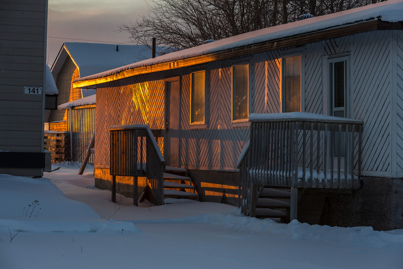 Sunlight lights up boards on wall of a building at the Niska Inn in Moosonee.