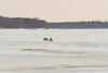 Snowmobile with sled crossing the Moose River.