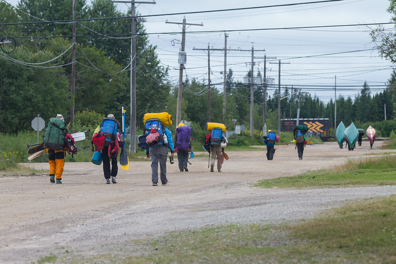 Canoeists heading to train station with canoes and gear.