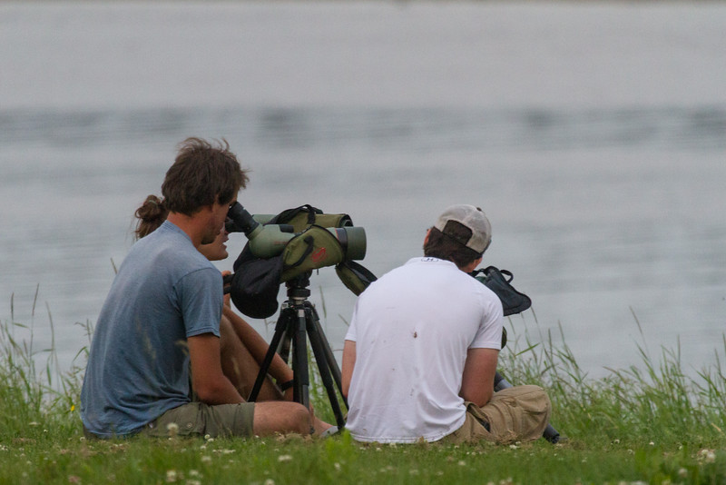 People on the riverbank in Moosonee using scopes.