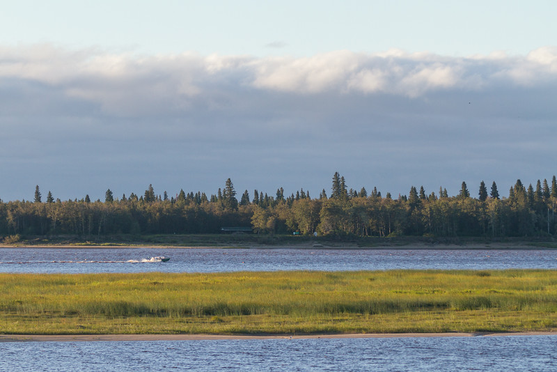 Taxi boat heading to Moose Factory. Clouds above Charles Island.