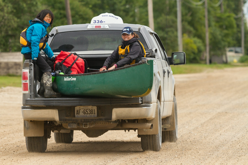 Back in Moosonee, articling students Laura Faryna (blue jacket) and Alyssa Holland head down Revillon Road in the back of a truck taxi.