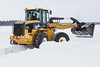 Snow removal at Keewaytinok Native Legal Services. Loader operated by Dan McKnight.