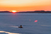 Snowmobile and sled on the Moose River at sunrise.