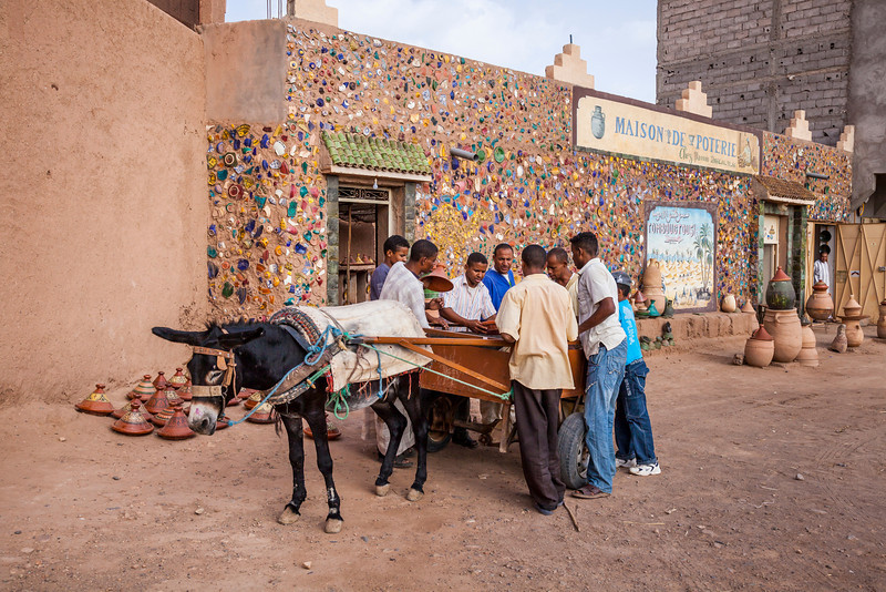 Men unloading a donkey at the souq of Tamegroute, Morocco.