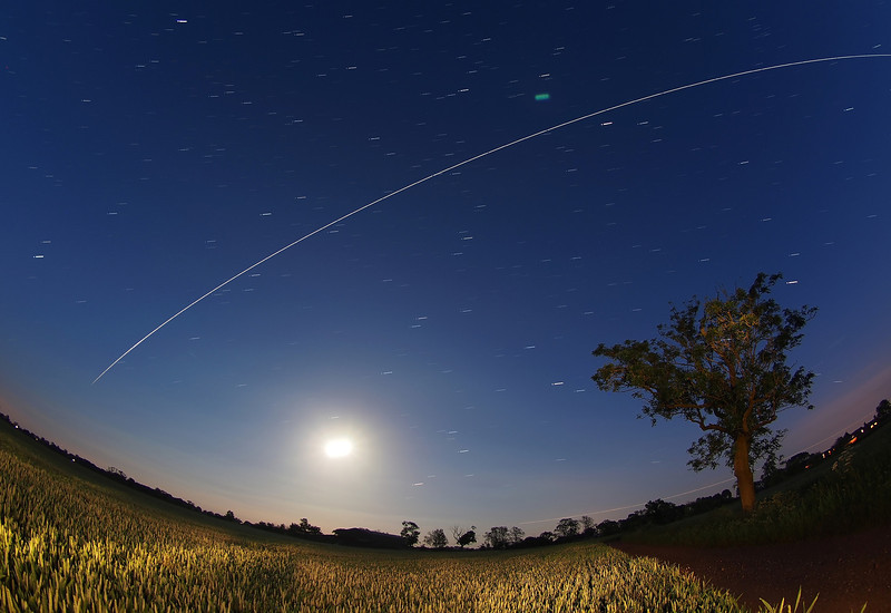 ISS flyby, 12 June 2014. The ISS delivers multiple flybys over UK skies during June allowing good opportunities to capture some or all, depending on cloud cover. This shot captures the 2259hrs pass. Especially dramatic as the flyby was a bit lower on the horizon and flew right over the moon fading out as the ISS enters Earth's shadow (love this).<br /> <br /> How did I capture this? Firstly, using my trusty GoSatWatch app I was able to predict the times and directions for all of the ISS passes (Well worthwhile download from the app store). I set my camera on a tripod pointing due south. Using a wide angle lens (8mm fisheye) I set camera in manual mode on a wide aperture (F4) and long exposure time of 15s and shot continuous exposures for the duration of the flyby (approx 15 No). When complete I hauled all the gear back indoors and downloaded. Using StarStax (Mac) software I imported each flyby exposure to generate a composite image. The long exposure time (15s) allowed the nearly full moon to shine out very bright. I lit the foreground with a large torch during exposure. <br /> <br /> Camera - Olympus OM-D, E-M5<br /> Lens - Olympus 8mm fisheye