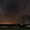 StarTrail 19 Jan 2014, Leicestershire, UK. A very narrow clear sky window in a very unsettled (and cloudy) winter thus far in the UK. Captured with Olympus OM-D E-M5. Leicester pollution clearly visible bottom left (orange glow). Thin high level clouds stated to roll in towards the end of this 3 hour capture, resulting in the orange linear streaks.<br /> How did I capture it? - Camera on tripod F4, ISO 400, 15s. Manual focus set to infinity I framed the tree ensuring polaris (north star) around which all other stars spin was located just to the left of tree. The first shot was captured/exposed through the lcd screen and then using the remote cable (set to lock) and turning off lcd (maximise battery) I depressed shutter. This allowed the camera to shoot continuous for three hours. With a bit of flash work I lit the tree and stood in front of the camera in differing locations to create the ghostly selfie :-) To complete the process I transferred all images (High res JPEG) to MAC and imported/stacked in StarStax software. Plane trails removed using Pixelmator software.