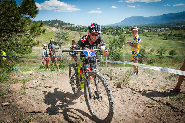 Todd Wells (Specialized) dismounts and runs his bike during the opening laps of the mens Pro XC race.