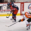 Kevin Harvey of Syracuse Crunch stops the puck while Garret Klotz of the Adirondack Phantoms moves in Sunday night at the Glens Falls Civic Center. Photo Eric Jenks 11/1/09.