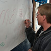Anthony Tobin leaves a message on thewelcome home banner for Sargent Andre Chao. Photo Eric Jenks 4/18/10