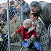 Alison Cape and Mike Douglass share a smile as 18 month old Eliot Cape pets a goat at the Fall Festival Sunday afternoon.