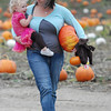 José Quezada/For the Times-Standard<br /> <br /> Lisa Sullivan is perhaps a little unsure which weighs more as she carries a pumpkin along with her 20-month old daughter Ayda Sullivan  from a pumpkin field on Sunday at Christie's Ranch in Blue Lake.