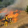 John Driscoll/The Times-Standard<br /> Eureka firefightes Ben Miller, left, and Kevin Stokes light a grass fire during a prescribed burn in Humboldt Redwoods State Park Wednesday.