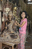 Burmese shot girl with a Buddha statues and a kinnayi behind the Buddha.  A kinnayi (kinnari) has the head, torso, and arms of a woman and the wings, tail and feet of a swan, and is a traditional symbol of feminine beauty, grace and accomplishment.