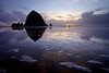 An evening beach stroller meanders amidst the bubbled reflections of Haystack Rock.