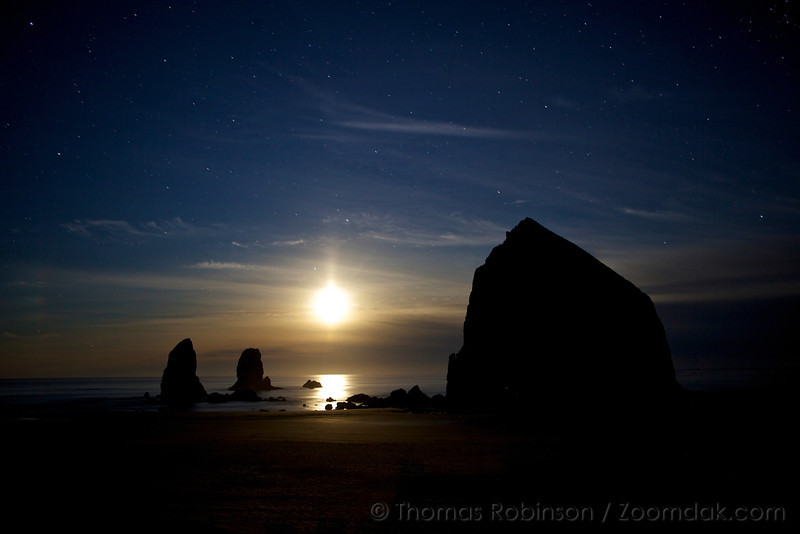 The moon sets between Haystack Rock and the needles with a starry night sky mixing in the cosmos and clouds.