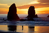 A couple strolls on the wet reflective sand below the Needles during a golden sunset in Cannon Beach, Oregon.