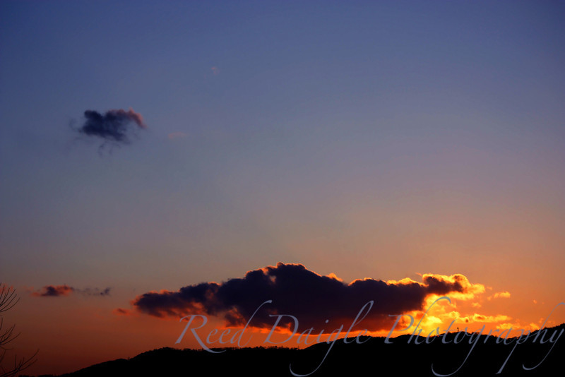 Sunset over mountains in rural Japan with dark purple clouds lined with golden glow