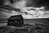 The old schoolhouse abandoned to the weather  and the elements; a dramatic scene desert, dark sky and decline.