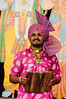 Indian man dancer wearing ared stripe turban and pink and white shirt<br /> Diwali celebration<br /> Aotea Square<br /> Auckland