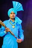 Indian man dancer in bright turquoise elaborate turban and long shirt<br /> Diwali celebration<br /> Aotea Square<br /> Auckland
