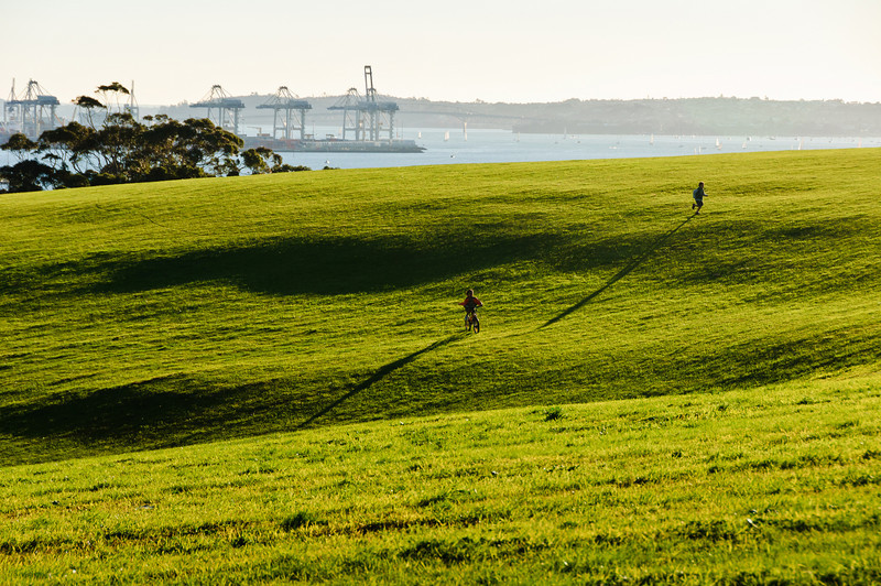 Kids gamboling across green meadows on a clear July afternoon at Bastion Point<br /> Auckland<br /> New Zealand