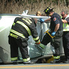 Newburyport: Salisbury firefighters work to free two young women, their heads popping through a window, from their rolled over vehicle on Route One in Salisbury across from David's Fish Market yesterday afternoon. The women were not injured. Bryan Eaton/Staff Photo
