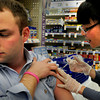 Newburyport: Walgreen pharmacist Hua Qi gives the flu shot to Tyler Dolan of Byfield in the Newburyport store yesterday. Hundreds have become ill from the strain this year in Massachusetts with close to a dozen deaths reported. Bryan Eaton/Staff Photo