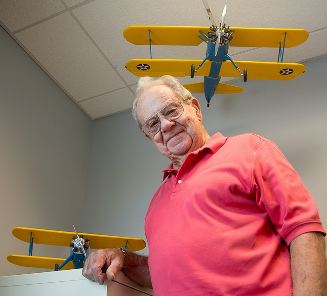 JIM VAIKNORAS/Staff photo<br /> <br /> Stuart Atkins poses at the Veteran Services office in Amesbury with two model planes he made.