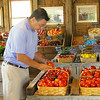 Seabrook Beach resident Buz Couillard picks out a few ripe tomatoes at  Bartlett's Farm Stand on Main Street to take with him for lunch.