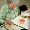 BRYAN EATON/Staff Photo. Ann Cote paints an amaryillis in watercolor class at the Amesbury Senior Center on Wednesday morning. Some of the paintings the group produce become birthday cards for attendees to the center.