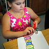 BRYAN EATON/ Staff Photo. Savannah Eaton, 7, cuts out her name to put on her school desk as she starts classes yesterday morning, It was the first day of school for Seabrook Elementary and Middle Schools.