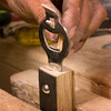 Greg puts in a glued shim to a bottle opener.