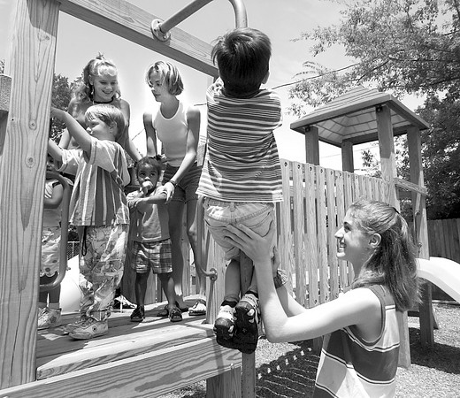 Jennifer Lynch, Kelly King and Stephanie King play with children before lunch on the playground at Asbury House in Longview.  Lester Phipps, Jr.