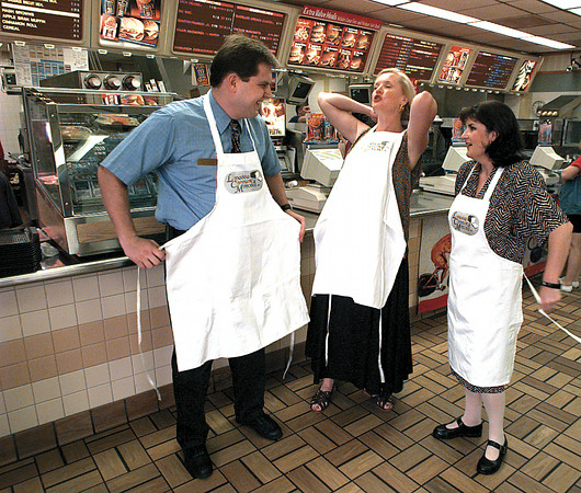 McDonalds manager Alan Benton, and volunteer Bobbie Robertson and Julie Buffington try on the new aprons that volunteers will be wearing........    Lester Phipps, Jr.