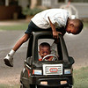Matthew Johnson, 5, checks to make sure his little brother Michael, 2, has his driver's liscence as they prepare to take off in their toy car in the 2100 block of 14th street recently. Chris Matula photo.