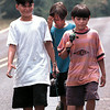 "Kevin Olvera, age 13, Cody Limburg-age 13 and 9-year-old Salvador Fernandez walk home from Lake Cherokee with their catch of the day.  ""We'll take 'em home, clean 'em and put 'em in the freezer with the others"", said Kevin.  Lester Phipps, Jr."