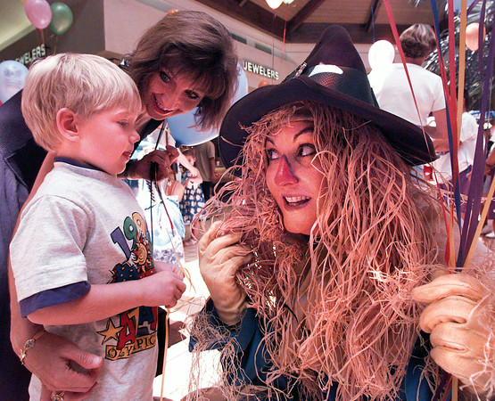 """Scarecrow Tina Bush tries to get 3-year-old Ryan Gillam to feel her """"hair"""" following her performance with other Junior League members at the Reading Rally at Longview Mall Friday.  Lester Phipps, Jr."""