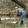 Dale Vodak with the TNRCC checks a still pool in a small creek next to the Sabine River Treatment plant Monday for traces of oil that spilled late Friday evening. Matula photo