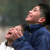 Brothers Osiel and Abraham Sanchez point their faces and mouths into the wind to catch the snowflakes as they fall.  Lester Phipps, Jr.